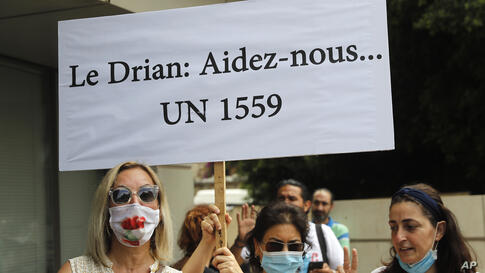 "Anti-Hezbollah protesters hold a French placard that reads:"" Drian (The family name of the French Foreign Minister) help us,""…"