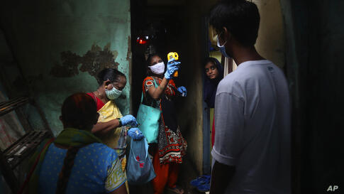 A health worker screens people for COVID-19 symptoms at Dharavi, one of Asia's biggest slums, in Mumbai, India, Monday, July 6,…