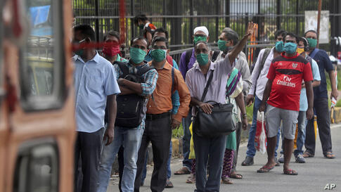 A man gestures to the driver of a bus as people wearing masks wait at a bus stop in Mumbai, India, Wednesday, July 22, 2020…