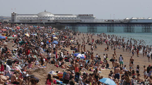 Beachgoers enjoy the sunshine and sea on what is now Britain's hottest day of the year so far, in Brighton, England, Friday,…