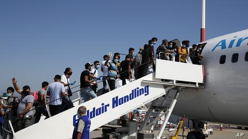 Migrants wearing face masks to prevent the spread of coronavirus, board an airplane bound for Iraq at the Eleftherios Venizelos…