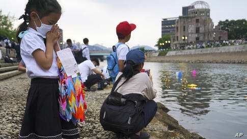 Saki Morioki, 5 years old, prays as paper lanterns float along the Motoyasu River in front of the Atomic Bomb Dome, Thursday,…