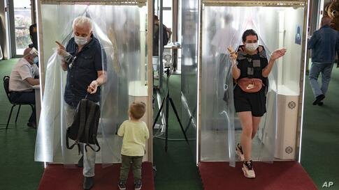 People wearing face masks and gloves to protect against coronavirus come through passages equipped with disinfectant sprays at…
