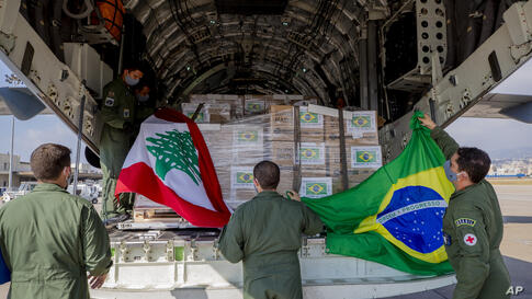 Brazilian air force personnel hold Brazilian and Lebanese flags on their arrival to the Beirut International Airport, in Beirut…