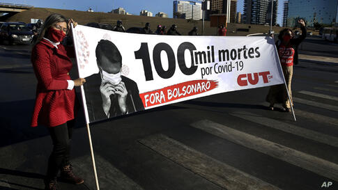 "Demonstrators hold a banner showing Brazil's President Jair Bolsonaro that reads in Portuguese ""100,000 deaths by COVID-19. Get…"