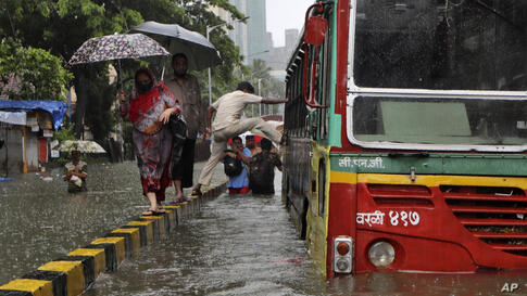 A man tries to get into a bus from a road median at a water logged street during heavy rain in Mumbai, India, Tuesday, Aug. 4,…