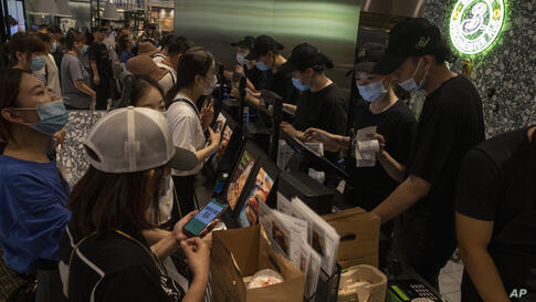 Customers line up to order at the first Beijing outlet for Shake Shack in Beijing Wednesday, Aug. 12, 2020. Antagonisms between…