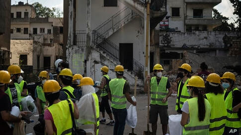 Volunteers from the American University of Beirut gather as they prepare to help remove debris in a neighborhood near the site…
