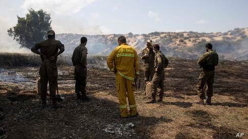 Israeli soldiers and a firefighter examine a fire started by an incendiary device launched from the Gaza Strip, on the Israeli…