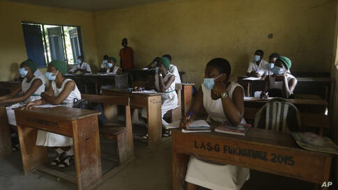 Students from Lagos State Model School wearing face mask to protect against coronavirus attend lectures inside a class room in…