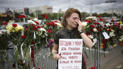 Alina Krus, 26, holds a poster at the place where a protester died amid the clashes in Minsk, Belarus, Wednesday, Aug. 12, 2020…