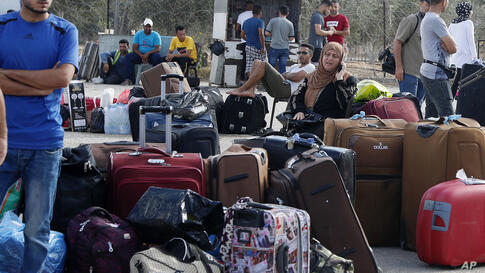 Passengers sit next to their luggage as they wait to cross the border to the Egyptian side of Rafah crossing, in Rafah, Gaza…