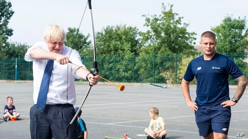 Britain's Prime Minister Boris Johnson takes part in archery during a visit to the Premier Education Summer Camp at Sacred…