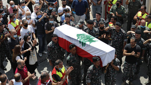 Firefighters carry the coffin of their comrade Rami Kaaki, one of ten firefighters who were killed during the last week's…