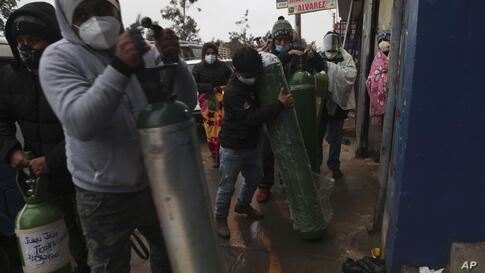People bring empty oxygen cylinders to refill at a shop in the San Juan neighborhood of Lima, Peru, Monday, Aug. 3, 2020…