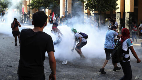 Protesters turn back tear gas canister against the Lebanese riot police, during anti-government protest following Tuesday's…