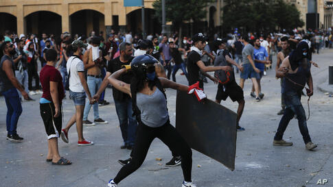 People throw stones during a protest following last week's explosion that killed many and devastated the city, in Beirut,…