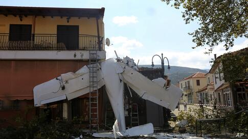 A small plane lays on a building after a crash in the village of Proti, near Serres town, northern Greece, on Monday, Aug. 3,…