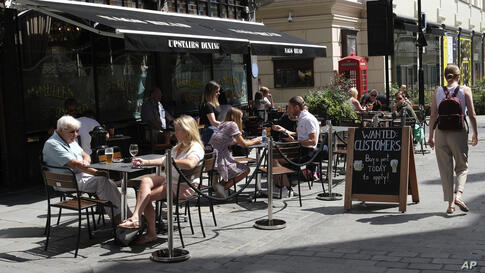 """A sign outside a pub that reads: """"Wanted Customers"""" in central London, Monday, Aug. 3, 2020. Restaurant discount meals """"Eat out…"""