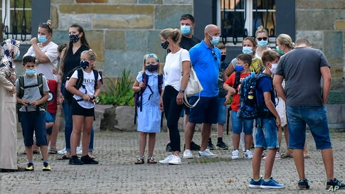 Parents wait with children on the schoolyard for the start of their first day at a school in Gelsenkirchen, Germany, Wednesday,…