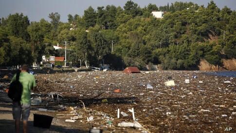 Debris covers the beach after a storm from the opposite island of Evia, as a man takes photographs in Chalkoutsi village, about…