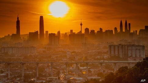 Sunset above the city center in Kuala Lumpur, Malaysia, on Monday, Aug. 10, 2020. (AP Photo/Vincent Thian)