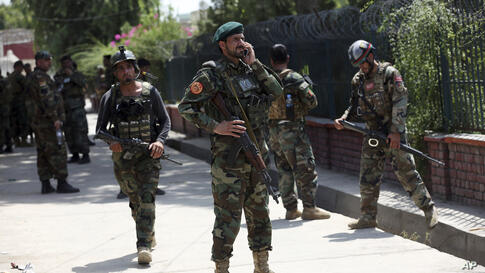 Afghan security personnel gather near a prison after an attack in the city of Jalalabad, east of Kabul, Afghanistan, Monday,…