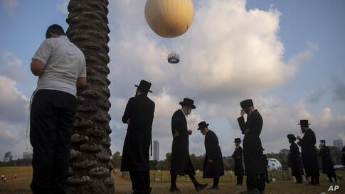 Ultra-Orthodox Jews, some wearing protective face mask amid concerns over the country's coronavirus outbreak, pray at a park in…