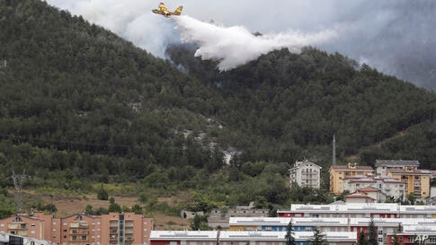 A Canadair plane drops water in the attempt to put out a fire in a hillside behind the town of Aquila, in the mountainous…