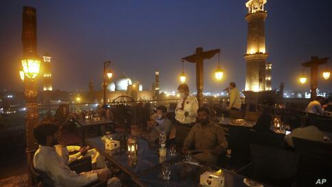 People eat at a rooftop restaurant close to the historical Badshahi Mosque, following an ease in restrictions that had been…