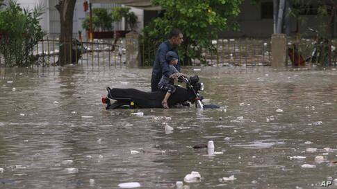 A motorcyclist navigate through a flooded street after a heavy rainfall in Karachi, Pakistan, Friday, Aug. 7, 2020. (AP Photo…