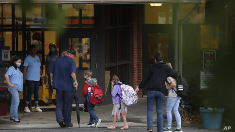 Students arrive to Dallas Elementary School for the first day of school amid the coronavirus outbreak on Monday, Aug. 3, 2020,…
