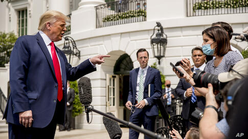 President Donald Trump speaks with members of the media before boarding Marine One on the South Lawn of the White House in…