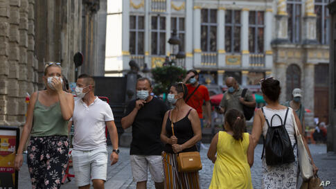 People wear protective face masks as they walk through the Grand Place in the historical center of Brussels, Wednesday, Aug. 12…