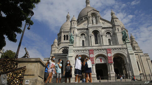 Tourists stroll by the Sacre Coeur basilica in the Montmartre district Monday, Aug. 10, 2020 in Paris. People are required to…