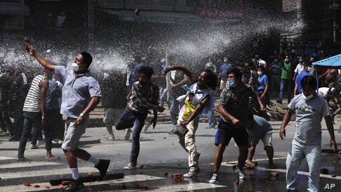 Nepalese protesters defying a government coronavirus lockdown to take part in a religious festival clash with riot police, in…