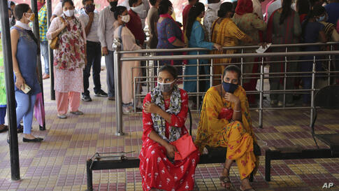 Indians wearing face masks wait for medical check-up outside a government hospital in Jammu, India, Wednesday, Sept.9, 2020…