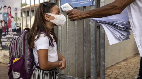An elementary school student wearing a mask has her body temperature checked amid the coronavirus pandemic as she enters school…