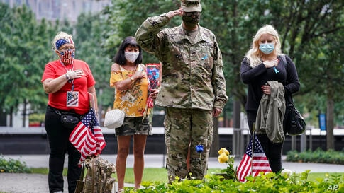 U.S. Army Sgt. Edwin Morales, center right, salutes after placing flowers for fallen FDNY firefighter Ruben D. Correa at the…
