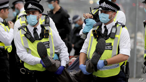 Police officers with face masks carry a protestor away during an Extinction Rebellion climate change protest at Parliament…
