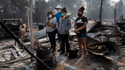 The Reyes family looks at the destruction of their home at Coleman Creek Estates mobile home park in Phoenix, Ore., Thursday,…