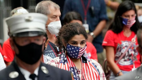 A woman wearing a flag mask joins others in prayer at the Tunnel to Towers ceremony, Sept. 11, 2020, in New York. Vice…