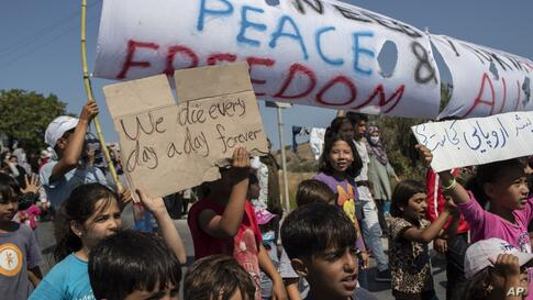 Migrants shout slogans during a protest near Mytilene town, on the northeastern island of Lesbos, Greece, Monday, Sept. 14,…