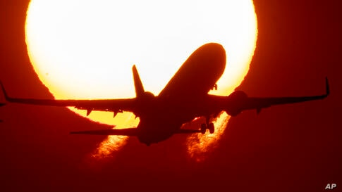 An aircraft takes off at the airport in Frankfurt, Germany, as the sun rises on Wednesday, Sept. 9, 2020. (AP Photo/Michael…