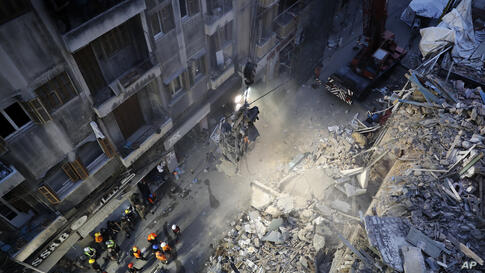 Rescuers work at he site of a collapsed building after getting signals there may be a survivor buried in the rubble, early…