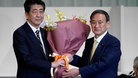 Japan's Prime Minister Shinzo Abe, left, receives flowers from Chief Cabinet Secretary Yoshihide Suga after Suga was elected as…