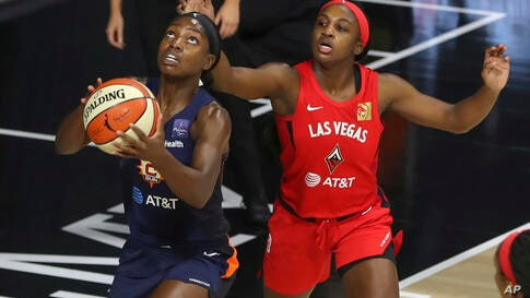 Connecticut Sun's Kaila Charles, left, drives past Las Vegas Aces' Jackie Young during the first half of a WNBA basketball game…