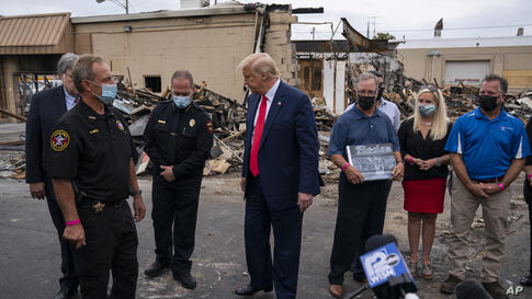 President Donald Trump speaks with business owners and law enforcement officials Tuesday, Sept. 1, 2020, as he tours an area…