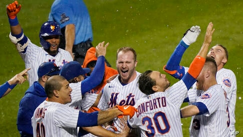 New York Mets' Pete Alonso, center, and teammates celebrate after Alonso hit a two-run home run during the 10th inning of the…