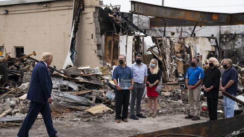 President Donald Trump speaks with business owners Tuesday, Sept. 1, 2020, as he tours an area damaged during demonstrations…